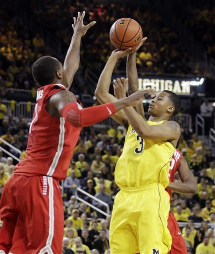Ohio State guard Lenzelle Smith Jr., rear, deflects a shot by Michigan guard Trey Burke (3) as Ohio State forward Deshaun Thomas (1) defends during the first half of an NCAA college basketball game in Ann Arbor, Mich., Saturday, Feb. 18, 2012. (AP Photo/Carlos Osorio)