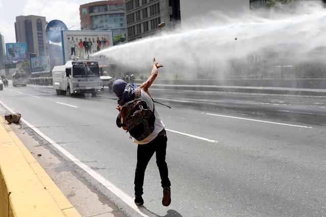 <p>A demonstrator throws a stone toward a water cannon vehicle during a rally against Venezuela's President Nicolas Maduro in Caracas, Venezuela, May 26, 2017. (Marco Bello/Reuters) </p>