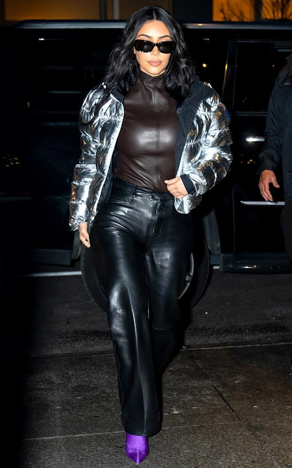 in a brown leather turtleneck, metallic puffer coat, black leather trousers and purple Balenciaga glove booties in N.Y.C.