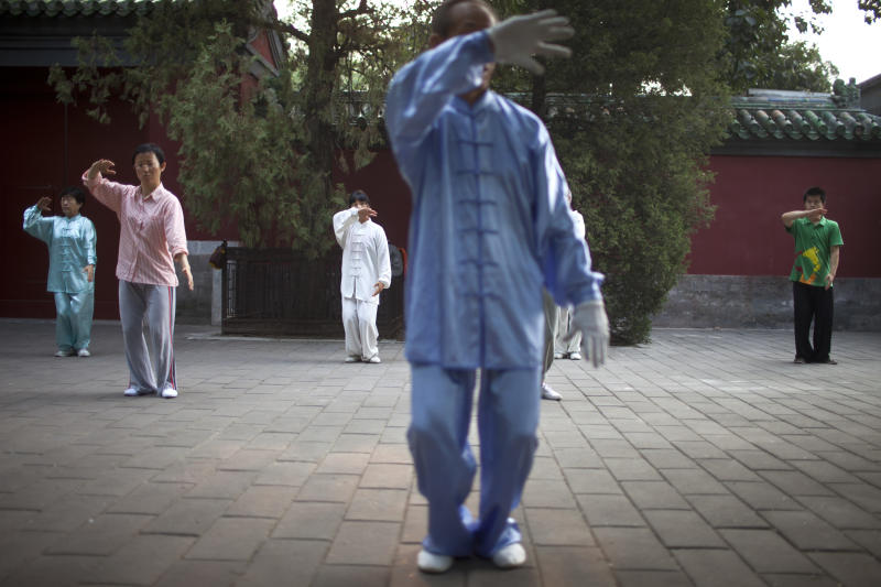 In this Tuesday, July 17, 2012 photo, people practice tai chi during their morning exercise at Ritan Park in Beijing, China. Some of the bigger parks in Beijing charge admission, but not Ritan Park, the historic garden where emperors once made offerings to the sun in an ancient circular wall-enclosed altar. (AP Photo/Alexander F. Yuan)