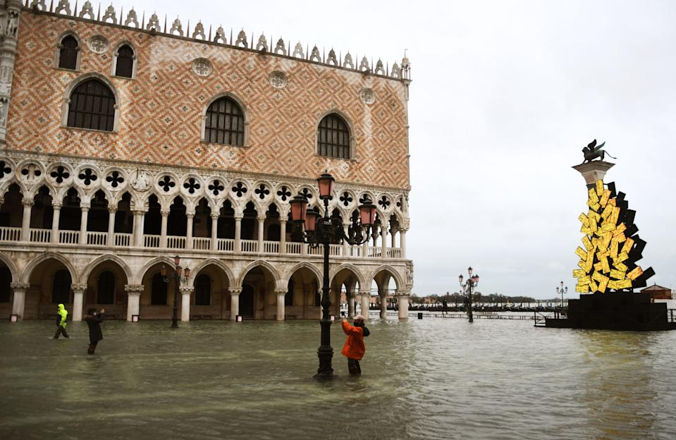 "A view shows a flooded St. Mark's Square with the Doge's Palace (Rear L) and a luminous Christmas Tree installation by Italian artist Fabrizio Plessi (Front R) on December 8, 2020 following a high tide ""Alta Acqua"" event following heavy rains and strong winds, and the mobile gates of the MOSE Experimental Electromechanical Module that protects the city of Venice from floods, were not lifted. (Photo by ANDREA PATTARO / AFP) / RESTRICTED TO EDITORIAL USE - MANDATORY MENTION OF THE ARTIST UPON PUBLICATION - TO ILLUSTRATE THE EVENT AS SPECIFIED IN THE CAPTION (Photo by ANDREA PATTARO/AFP via Getty Images)"