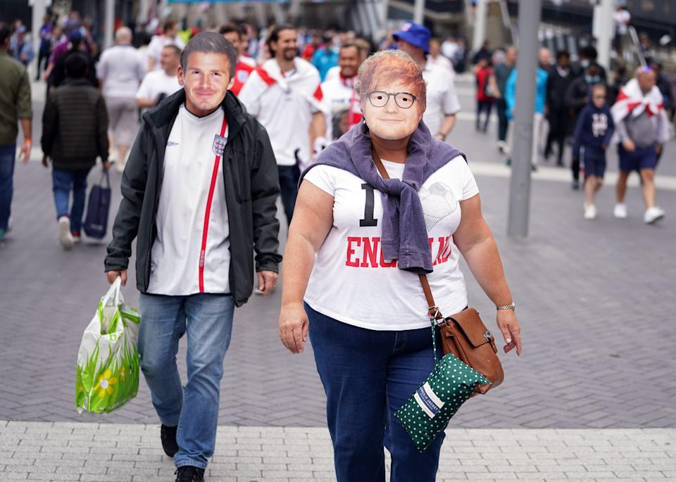 England fans sporting facemasks of Ed Sheeran and David Beckham outside Wembley Stadium ahead of the Euro 2020 semi-final match between England and Denmark (PA Wire)