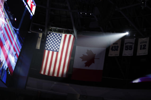 American flag illuminated during playing go the National Anthem in the first period of an NHL hockey game Tuesday, Jan. 2, 2018, in Denver. (AP Photo/David Zalubowski)