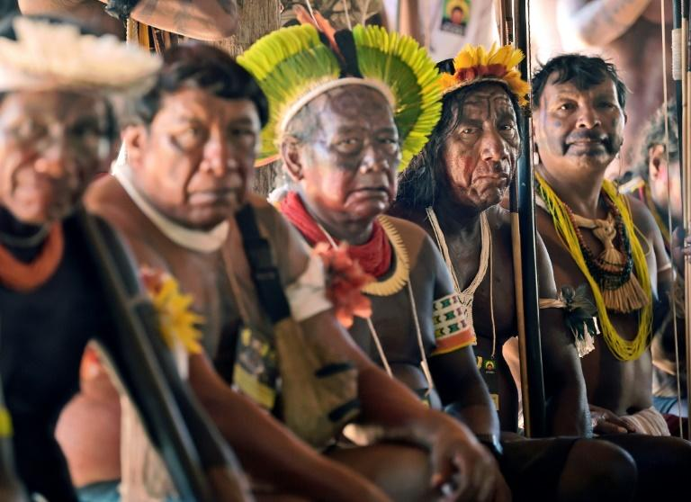 Indigenous tribesmen listen to chief Raoni Metuktire (out of frame) during a press conference in Piaracu village, near Sao Jose do Xingu, Mato Grosso state, Brazil (AFP Photo/CARL DE SOUZA)