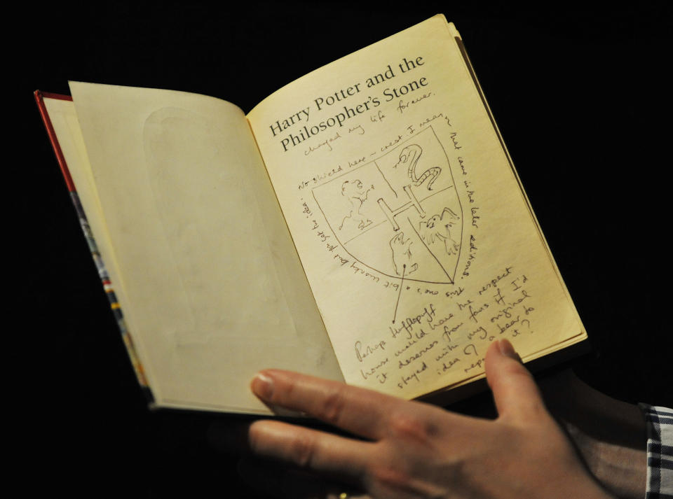 Dr Philip Errington, director of printed books and manuscripts at Sotheby's in London holds a first editor Harry Potter book annotated by author JK Rowling. (Nick Ansell/PA Wire)