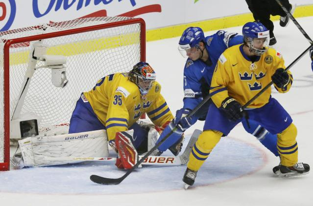 Finland's Rasmus Ristolainen (C) scores the game winning goal on Sweden's goalie Oscar Dansk (L) and Robin Norell during overtime of their IIHF World Junior Championship gold medal ice hockey game in Malmo, Sweden, January 5, 2014. REUTERS/Alexander Demianchuk (SWEDEN - Tags: SPORT ICE HOCKEY)
