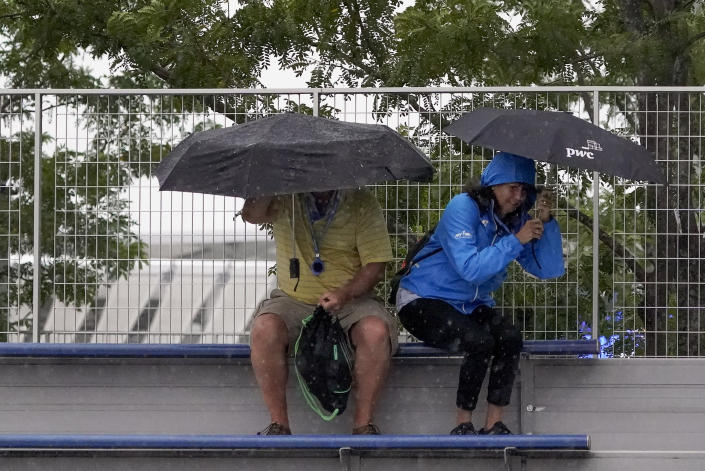 Tennis fans take cover under umbrellas as rain begins to fall during the second round of the US Open tennis championships, Wednesday, Sept. 1, 2021, in New York. (AP Photo/Elise Amendola)