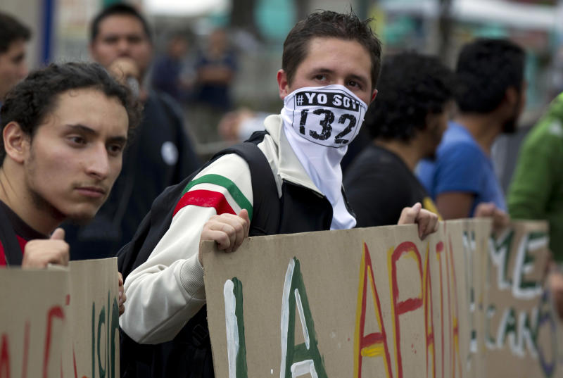 "A student of the #Yo Soy 132 or ""I am 132"" movement wears a face mask as he demonstrates outside of the Federal Electoral Tribunal in Mexico City, Thursday, Aug. 30, 2012. Three of the seven justices on Mexico's highest election court, the Federal Electoral Tribunal, recommended Thursday dismissing legal challenges mounted by the second-place leftist candidate that seek to overturn the results of the July 1 presidential elections. The ""I am 132"" movement began in opposition of the alleged biased coverage by the media of the 2012 elections and against the candidacy of Enrique Pena Nieto of the Revolutionary Institutional Party (PRI). (AP Photo/Eduardo Verdugo)"