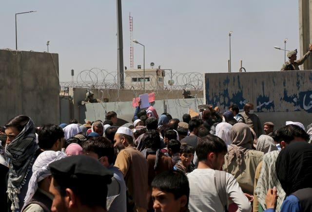 US soldiers stand inside the airport wall as hundreds of people gather near an evacuation control checkpoint on the perimeter of the Hamid Karzai International Airport in Kabul, Afghanistan