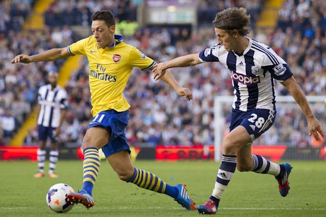 Arsenal's Mesut Ozil, left, keeps the ball from West Bromwich Albion's Billy Jones during their English Premier League soccer match at The Hawthorns Stadium, West Bromwich, England, Sunday Oct. 6, 2013. (AP Photo/Jon Super)