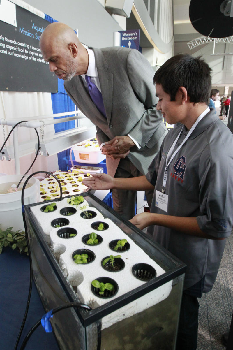 Victor Contreras, an 11th grader at Citrus Hill High School, in Riverside County, explains his school's project to grow affordable produce using hydroponics and aquaculture to basketball legend Kareem Abdul-Jabbar during an education seminar in Sacramento, Calif., Monday, Nov. 18, 2013. Educators from around the state gathered for the first annual California STEM (science, technology, engineering and math) Symposium to present teachers and administrators with classroom strategies. Abdul-Jabbar is the founder of the Skyhook Foundation which encourages mentor-led educational programs such as STEM. (AP Photo/Rich Pedroncelli)