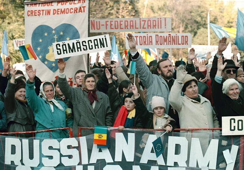 """Moldovan people protest in front of a banner reading """"Russian army go home,"""" in the capital Chisinau in 2003"""