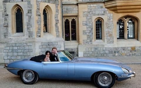 Harry and Meghan in a classic E-Type Jaguar heading off to their wedding reception