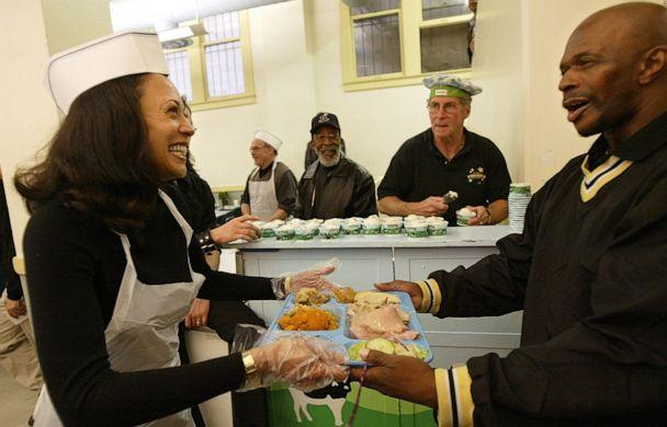 PHOTO: Then San Francisco district attorney candidate Kamala Harris, left, serves lunch to an unidentied visitor while volunteering at Thanksgiving service at Glide Memorial United Methodist Church in San Francisco on Thursday, Nov. 27, 2003. (Jeff Chiu/AP Photo)