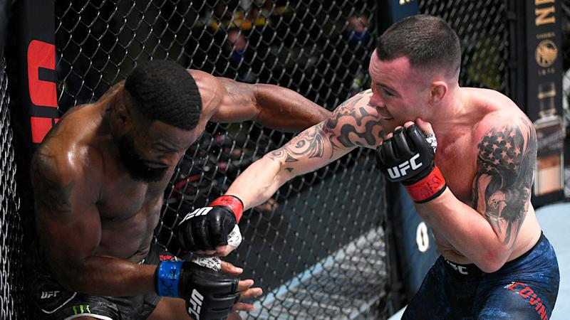 Pictured here, Colby Covington hits Tyron Woodley with a fierce right hand in their UFC bout.
