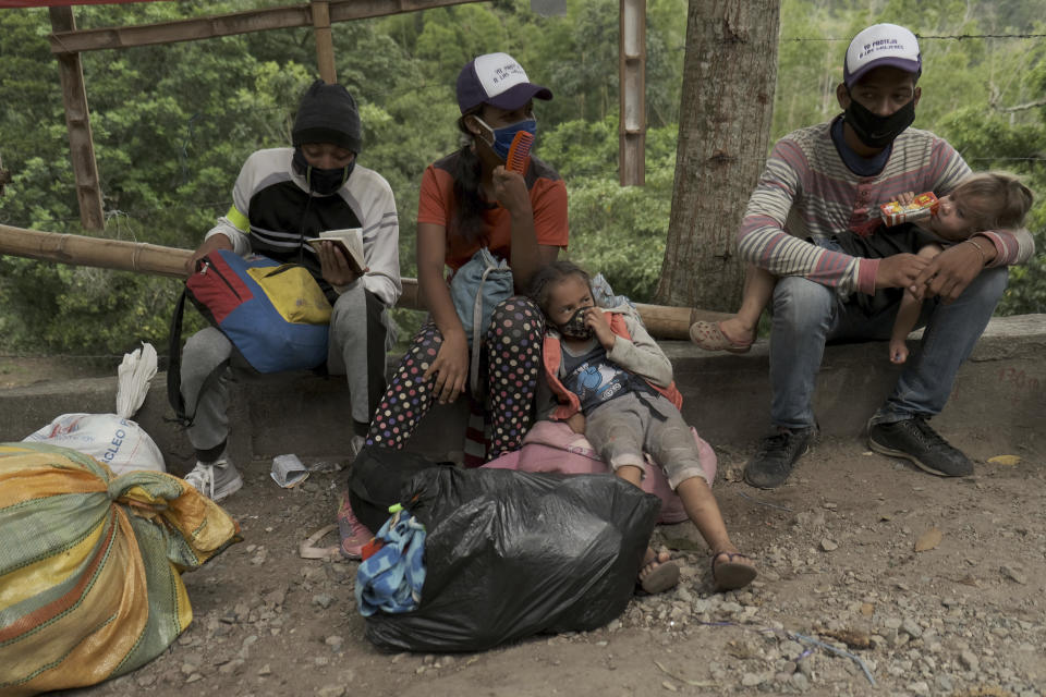 Venezuelan migrants rest as they walk away from the Venezuelan border toward Pamplona, Colombia, Wednesday, Oct. 7, 2020. Colombian immigration officials expect 200,000 Venezuelans to enter the country in the months ahead, enticed by the prospects of earning higher wages and sending money back to Venezuela to feed their families. (AP Photo/Ferley Ospina)