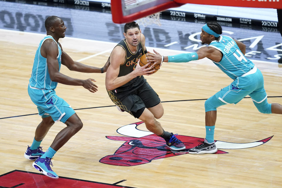 Chicago Bulls' Nikola Vucevic, center, drives to the basket between Charlotte Hornets' Devonte' Graham (4) and Bismack Biyombo during the first half of an NBA basketball game Thursday, April 22, 2021, in Chicago. (AP Photo/Charles Rex Arbogast)