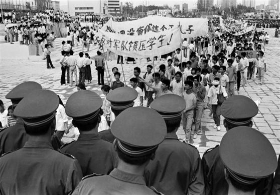 Chinese police monitor a march by tens of thousands of pro-democracy protesters in the special economic zone of Shenzhen in southern China, May 22, 1989.