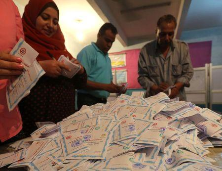 Electoral workers count ballots during the third day of voting in Egypt's presidential election at a polling station in Cairo