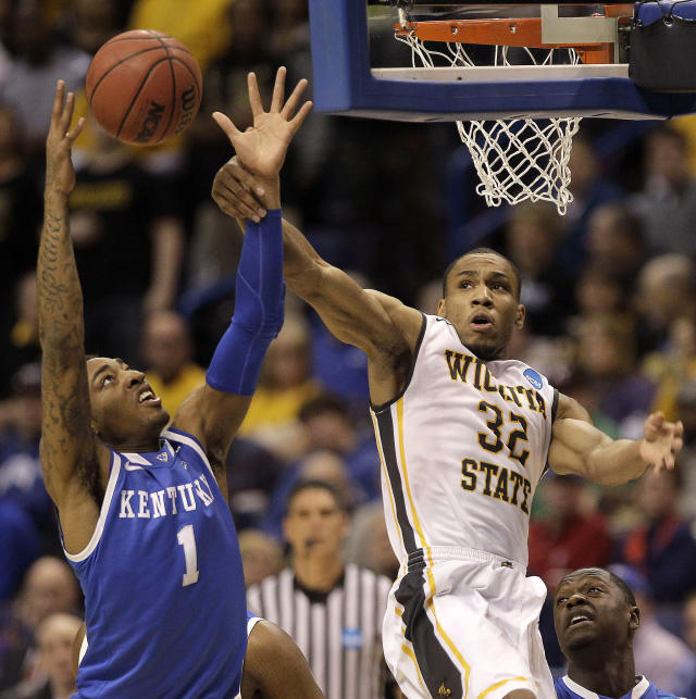 Wichita State's Tekele Cotton (32) and Kentucky's James Young (1) battle for a rebound during the first half of a third-round game at the NCAA college basketball tournament Sunday, March 23, 2014, in St. Louis. (AP Photo/Charlie Riedel)