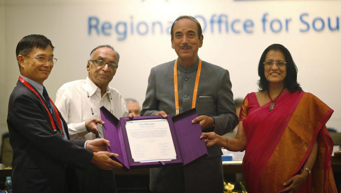 Chairperson of South-East Asia Regional Certification Commission for Polio Eradication Supamit Chunsuttiwat, left, and WHO's South-east Asian region Regional Director Poonam Khetrapal, right, give polio free certification to Indian Health Minister Ghulam Nabi Azad, second right, and Indian official P.K Umashankar, second left, in New Delhi, India, Thursday, March 27, 2014. The World Health Organization has formally declared India polio-free, with no new case of the disease detected in the country in the past three years. (AP Photo/Saurabh Das)