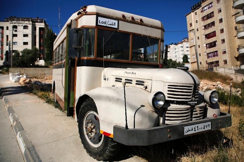 Youths are restoring a bus to preserve the memory of the days before the Six-Day War in 1967 when Palestinian buses ferried passengers around the Middle East (AFP Photo/ABBAS MOMANI)