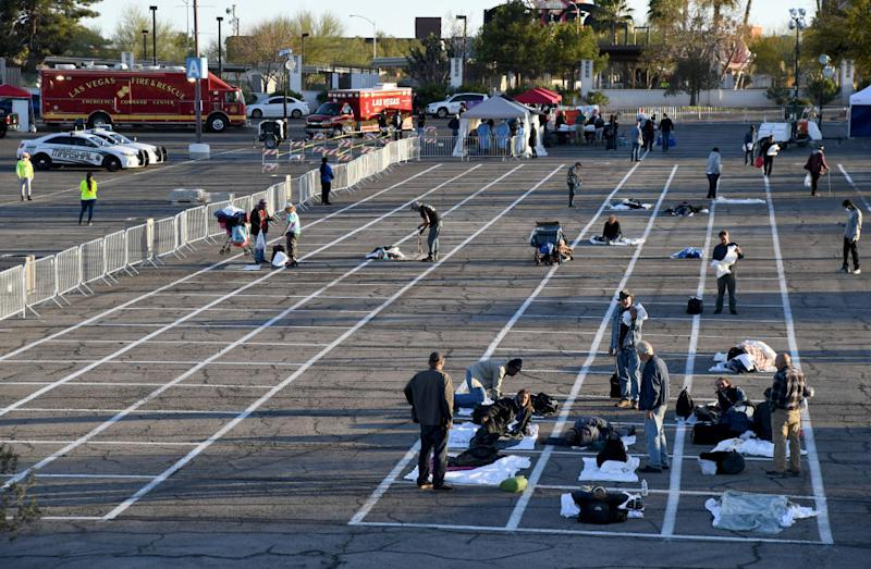 Homeless people sit in painted squares at a Las Vegas carpark.