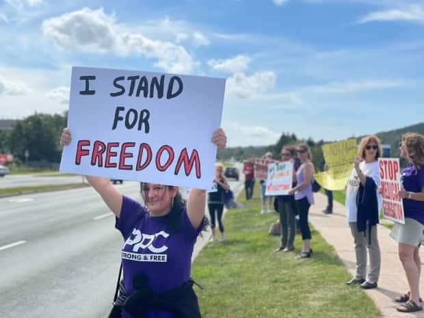 A protester holds a sign at an anti-vaccine passport protest in St. John's on Monday. (Meg Roberts/CBC - image credit)