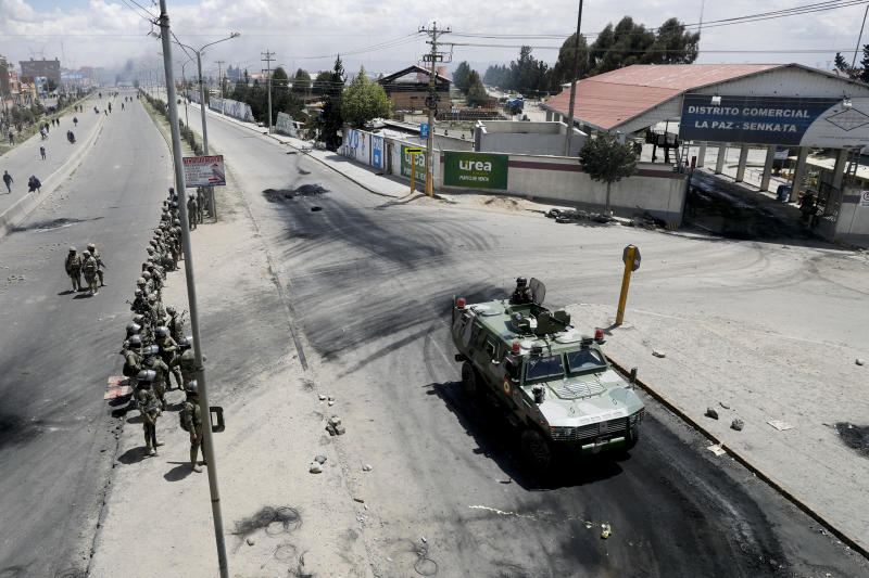 Soldiers guard the state-own Senkata filling gas plant in El Alto, on the outskirts of La Paz, Bolivia, Tuesday, Nov. 19, 2019. Backers of former President Evo Morales have taken to the streets asking for his return since he resigned on Nov. 10 under pressure from the military after weeks of protests against him over a disputed election he claim to have won. (AP Photo/Natacha Pisarenko)