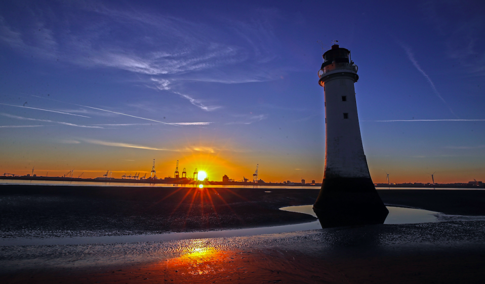 <em>The sun rises behind the lighthouse at New Brighton beach on the Wirral, Merseyside (PA)</em>
