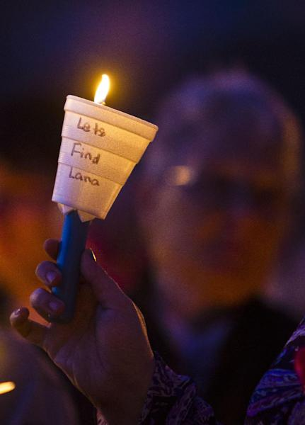 A candle burns during a prayer vigil for Lana-Leigh Bailey and the other victims at Forest Park Friday, May 10, 2013 in Ottawa, Kan. Kyle Flack, a 27-year-old convicted felon was charged Friday in the deaths of a woman and two men whose bodies were found at an eastern Kansas farm home earlier this week, according to a criminal complaint. (AP Photo/The Kansas City Star, Allison Long)