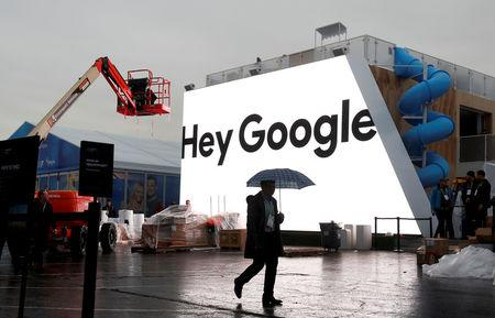 FILE PHOTO: A man walks through light rain in front of the Hey Google booth under construction at the Las Vegas Convention Center in preparation for the 2018 CES in Las Vegas