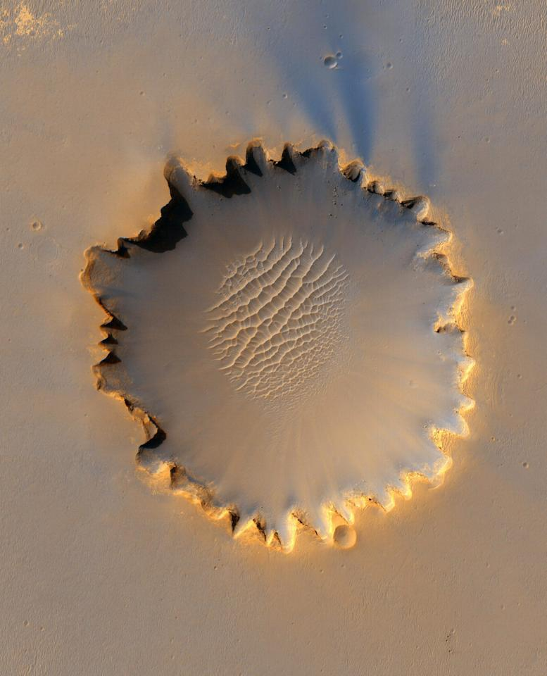 Mars' Victoria Crater at Meridiani Planum is seen in this image taken by NASA's High Resolution Imaging Science Experiment (HiRISE) camera in this picture released October 6, 2006.  NASA officials gave conflicting views during a meeting of space scientists on December 13, 2006, on whether the construction of a moon base will mark a great leap in planning for a manned mission to Mars or prove a wasteful diversion of funds.  FOR EDITORIAL USE ONLY REUTERS/NASA/JPL/Caltech/Handout (UNITED STATES)