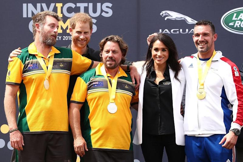 Harry and Meghan pose with gold medalists Cedric Arci and Michael Ranchin of France and Silver medallists Craig McGrath and Scott Reynolds of Australia during the medal ceremony of the JLR Drive Day (Getty Images)