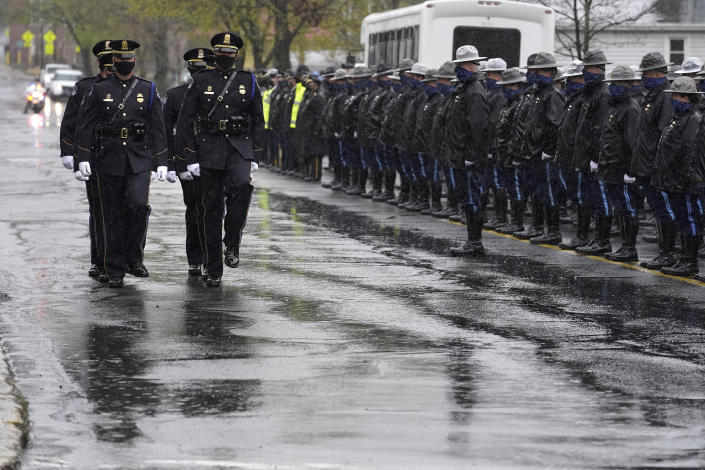 """Pallbearers from the U.S. Capitol Police, left, process past Massachusetts state police, right, as they approach St. Stanislaus Kostka Church before a funeral Mass for William """"Billy"""" Evans, Thursday, April 15, 2021, in Adams, Mass. Evans, a member of the U.S. Capitol Police, was killed on Friday, April 2, when a driver slammed his car into a checkpoint he was guarding at the Capitol. (AP Photo/Steven Senne)"""