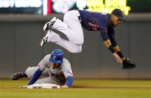 Minnesota Twins shortstop Pedro Florimon, top, leaps after making the out at second base against Texas Rangers' Ian Kinsler, bottom, during the third inning of a baseball game on Thursday, April 25, 2013, in Minneapolis. (AP Photo/Genevieve Ross)