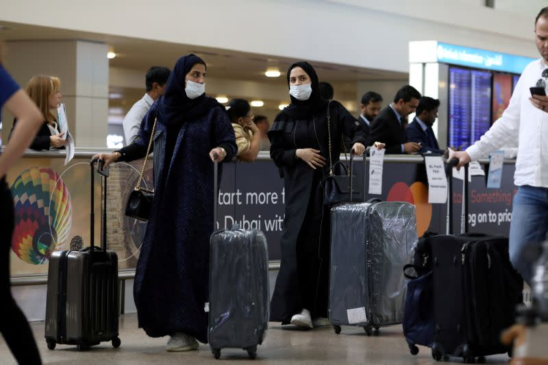 Travellers wear masks as they arrive at Dubai International Airport, after the UAE's Ministry of Health and Community Prevention confirmed the country's first case of coronavirus, in Dubai