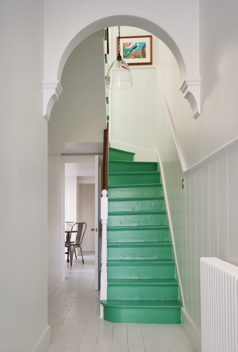 <p>London-based designer Olivia Outred brings a fresh, vibrant pop of color in this otherwise monochromatic entry. A rich green in a warm and inviting hue is the perfect welcome for guests as they pass the threshold into your home. An abstract painting at the top of the stairs and delightful architectural details tie this charming space together. </p>