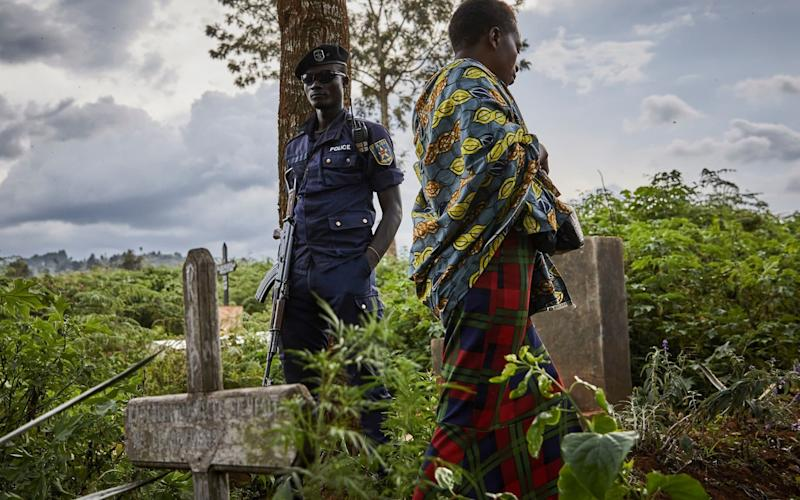 A police officer guards the funeral of Ebola victims in Butembo - REX