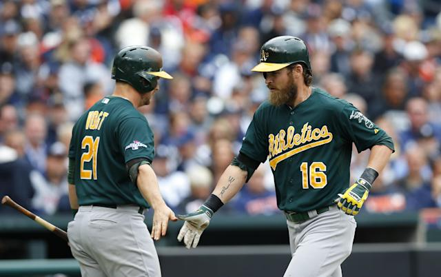 Oakland Athletics' Josh Reddick (16) is greeted by teammate Stephen Vogt after hitting a solo home run off Detroit Tigers starting pitcher Anibal Sanchez during the fourth inning of Game 3 of an American League baseball division series in Detroit, Monday, Oct. 7, 2013. (AP Photo/Paul Sancya)