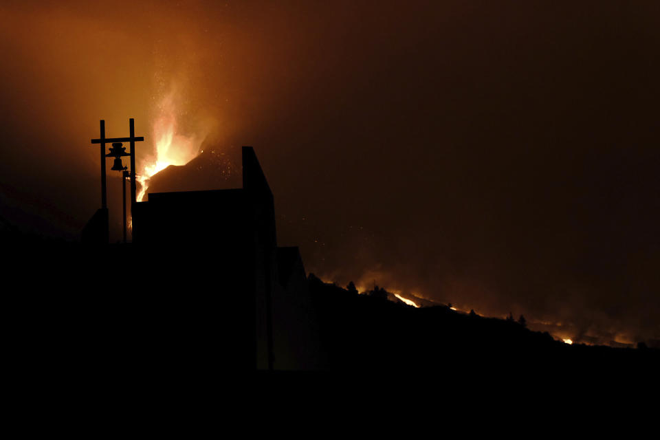 A volcano continues to spew out lava behind a church in Tajulla on the Canary island of La Palma, Spain in the early hours of Sunday, Oct. 10, 2021. A new river of lava has belched out from the La Palma volcano, spreading more destruction on the Atlantic Ocean island where molten rock streams have already engulfed over 1,000 buildings. The partial collapse of the volcanic cone has sent a new lava stream heading toward the western shore of the island. (AP Photo/Daniel Roca)