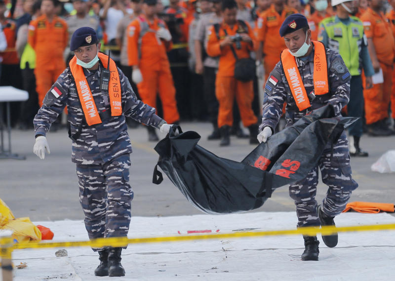 "FILE - In this Thursday, Nov. 1, 2018, file photo, navy personnel carry the remains of a victim of Lion Air jet that crashed into the sea at the Tanjung Priok Port in Jakarta, Indonesia. Boeing Co. says it has issued a safety bulletin that reiterates guidelines on how pilots should respond to erroneous data from an ""angle of attack"" sensor following last week's crash of a Boeing plane in Indonesia that killed 189 people. (AP Photo/Tatan Syuflana, File)"