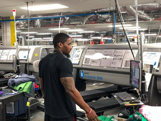 A worker operates the Kornit Digital printing machine in Amazon facility. (Credit: Amazon)