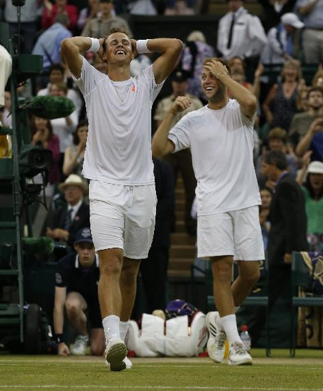 Vasek Pospisil of Canada, left, and Jack Sock of the U.S celebrate defeating Bob Bryan and Mike Bryan of the U.S in the men's doubles final at Wimbledon. (AP Photo/Sang Tan)