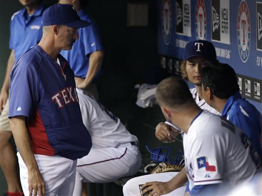 Texas Rangers pitching coach Mike Maddux, left, and catcher Mike Napoli, front center, talk with starting pitcher Yu Darvish, right rear, and his interpreter, right, following the top of the first inning of a baseball game against the Seattle Mariners Monday, April 9, 2012, in Arlington, Texas. (AP Photo/Tony Gutierrez)