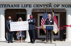 L to R: Retired Brigadier General Thomas Gorry-VLC Executive Director, Jama Campbell-SECU Foundation Executive Director, and John Turner-VLC Founder & Senior Advisor holding ceremonial check during presentation by Mike Lord, SECU President & CEO.