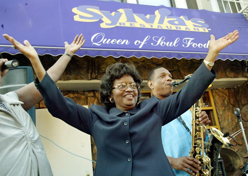 "FILE- In this Aug. 1, 2002 file photo, Sylvia Woods, center, moves to the music outside her restaurant, ""Sylvia's,"" during the restaurant's 40th anniversary celebration, in the Harlem neighborhood of New York. Woods died in Mount Vernon, N.Y. on Thursday, July 19, 2012. She was 86. (AP Photo/Stuart Ramson, File)"