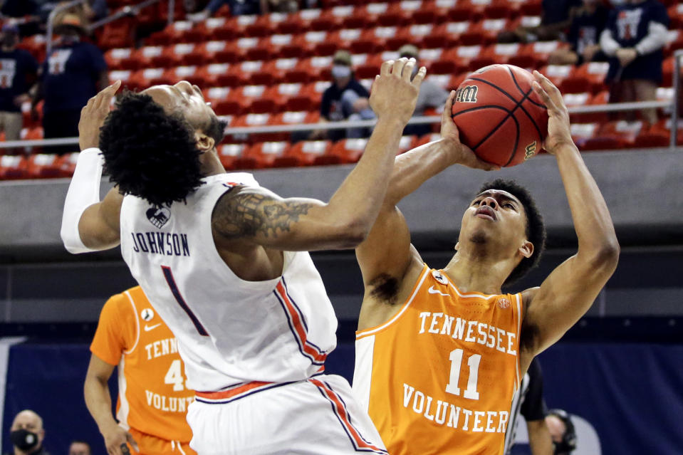 Auburn guard Jamal Johnson (1) collides with and fouls Tennessee guard Jaden Springer (11) as he takes a shot during the second half of an NCAA basketball game Saturday, Feb. 27, 2021, in Auburn, Ala. Auburn won 77-72. (AP Photo/Butch Dill)