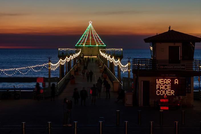 "Holiday lights cover a pier at sunset as an electric sign reads ""Wear a face cover."""