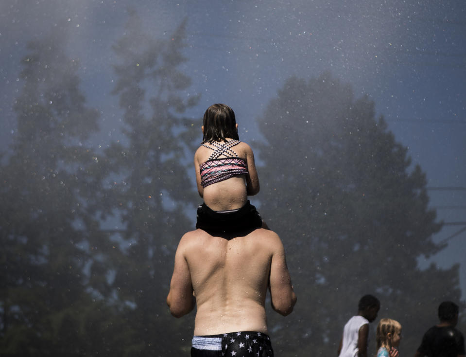 People stand in the spray from the Everett Fire Department's fire hose sprinkler station at Walter E. Hall Park on Saturday, June 26, 2021 in Everett, Wa. (Olivia Vanni/The Daily Herald via AP)